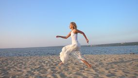 happy young beautiful woman running and jumping on the beach