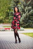 Happy young fashion woman in floral dress in city park royalty free stock photography