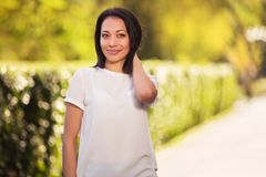 Happy young fashion woman in white t-shirt in city park royalty free stock photography