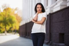 Happy young fashion woman in white t-shirt on city street royalty free stock photos