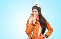 Happy young beautiful women in winter clothes surprised isolated on blue background royalty free stock photo