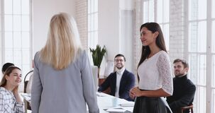 Young female worker being appreciated promoted handshake older executive