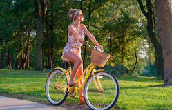 Happy young bicyclist riding in city. Beautiful woman on bike, during summer royalty free stock image