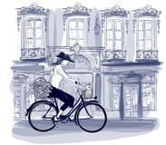 Happy young bicyclist riding in a street in Paris with a little stock illustration