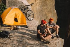 happy young bike travellers with canned food sitting royalty free stock photography
