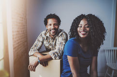 Happy young black african couple moving boxes into new apartment together and making a successful life.Cheerful family stock photos