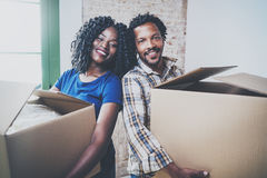 Happy young black african man and his girlfriend moving boxes into new house together and making a successful life. Happy young black african men and his royalty free stock photography