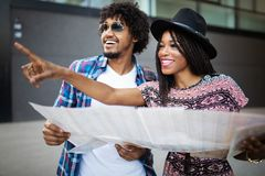 Happy young black couple of travellers holding map in hands stock photo