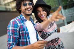 Happy young black couple of travellers holding map in hands. Happy young african couple of travellers holding map in hands stock photography