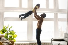 Happy african father lifting up in air little son royalty free stock photo