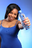 Happy young black girl holding out bottled water Stock Images