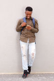 Happy young black guy smiling with cellphone and bag Royalty Free Stock Photo