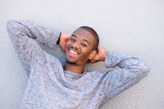 Happy young black guy smiling with hands behind head Royalty Free Stock Image