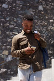 Happy young black male student laughing with cell phone. Portrait of happy young black male student laughing with cell phone Stock Photo