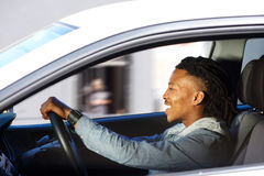 Happy young black man driving car. Side portrait of happy young black man driving car Royalty Free Stock Photos