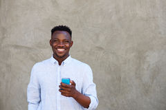 Happy young black man with mobile phone standing by wall Royalty Free Stock Photography