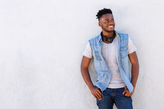 Happy young black man standing by wall with headphones Royalty Free Stock Photos