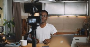 Happy young black popular social media blogger man live streaming for his online blog using camera at home slow motion. Blogging and vlogging as modern stock video