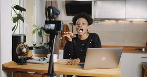 Happy young black travel blogger woman making new vlog video with camera at home, laughing and talking slow motion. Beautiful African female vlogger creating stock video footage