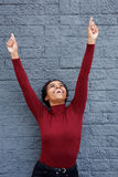Happy young black woman with arms raised and fingers pointing up Stock Photo