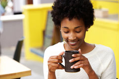 Happy young black woman drinking coffee stock photos