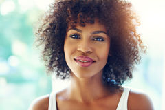 Happy young black woman with frizzy hair. Portrait of happy young black woman relaxing in bright sunshine royalty free stock images