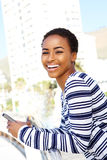 Happy young black woman holding cellphone outside Royalty Free Stock Photography