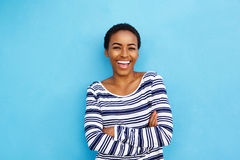 Happy young black woman laughing against blue wall. Portrait of happy young black woman laughing against blue wall royalty free stock image