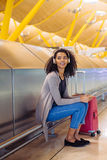 happy young black woman listening music with headphones and mobile phone at the airport royalty free stock photos