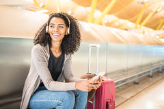 happy young black woman listening music with headphones and mobile phone at the airport royalty free stock photography
