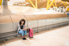 happy young black woman listening music with headphones and mobile phone at the airport royalty free stock images