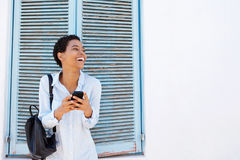Happy young black woman with mobile phone and bag Royalty Free Stock Images