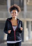 Happy young black woman running outdoors Stock Images