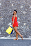 Happy young black woman with shopping bags talking on cellphone Stock Photo