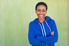 Happy young black woman smiling against green background Royalty Free Stock Photos