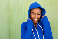 Happy young black woman smiling against green wall Stock Photos