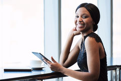 Happy young black woman smiling at the camera with tablet stock images