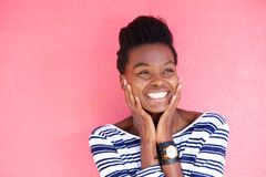 Happy young black woman smiling with hands on face Royalty Free Stock Images