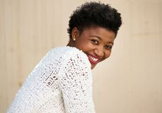 Happy young black woman smiling in white sweater. Close up portrait of a happy young black woman smiling in white sweater stock photography