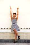 Happy young black woman in striped dress pointing fingers up. Full length portrait of happy young black woman in striped dress pointing fingers up Royalty Free Stock Image
