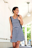 Happy young black woman in striped dress walking outdoors Stock Images