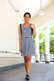 Happy young black woman in striped dress walking outside Royalty Free Stock Images