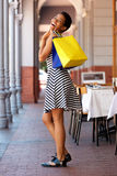 Happy young black woman in striped dress walking with shopping bags Stock Photo