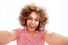 Happy young black woman taking selfie against white background stock images