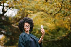 Stylish black woman taking selfie with smartphone in autumn Stock Photos