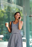 Happy young black woman walking and talking on cellphone Royalty Free Stock Photos
