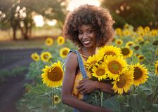 Happy young black woman walks in the sunflower field. Smiling dark-skinned girl with with a bouquet of sunflowers and