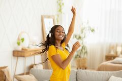 Free Happy Young Black Woman With Headphones And Mobile Device Dancing To Her Favorite Music At Home Stock Image - 196319211