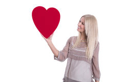 Happy young blond caucasian woman Holding red heart. Royalty Free Stock Image