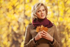 Happy young blond fashion woman in classic beige coat walking outdoor royalty free stock images